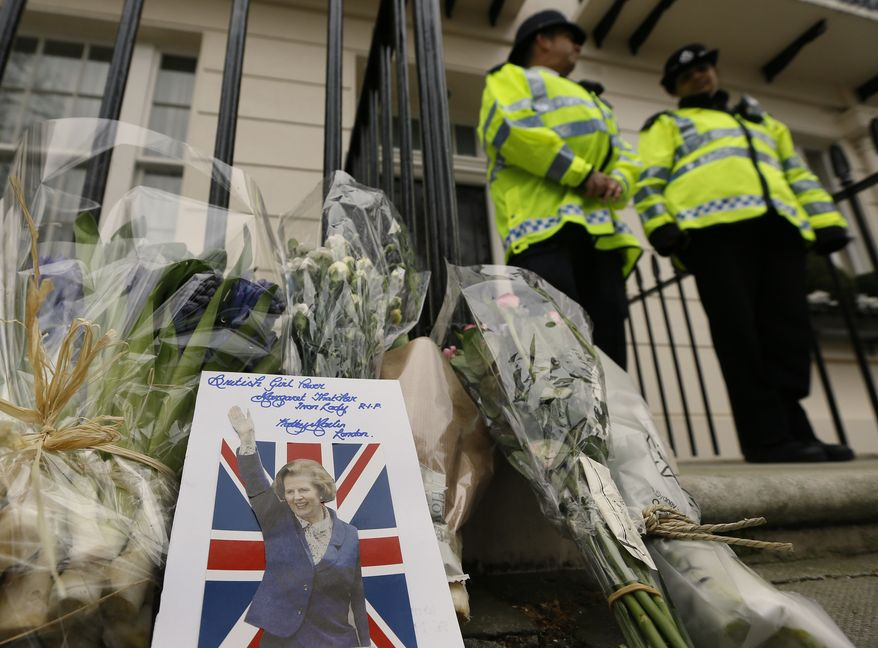 A card is left on a floral tribute outside former British Prime Minister the Baroness Thatcher's home in London on Tuesday, April 9, 2013. (AP Photo/Kirsty Wigglesworth)