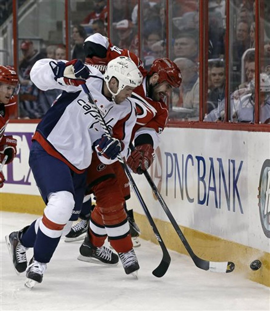 Washington Capitals' Brooks Laich (21) and Carolina Hurricanes' Jay Harrison (44) chase the puck during the first period of an NHL hockey game in Raleigh, N.C., Tuesday, April 2, 2013. (AP Photo/Gerry Broome)