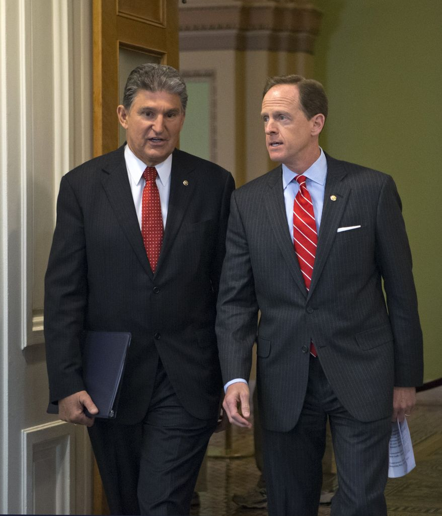 Sen. Joe Manchin of West Virginia, D-W.Va., left, and Sen. Patrick Toomey, R-Pa., arrive at a news conference on Capitol Hill in Washington, Wednesday, April 10, 2013, to announce that they have reached a bipartisan deal on expanding background checks to more gun buyers. (AP Photo/J. Scott Applewhite)