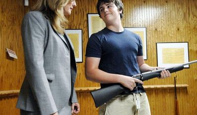 ** FILE ** Michael Steelman (right), 13, smiles at his mother, Missouri state Treasurer Sarah Steelman, after picking out a rifle while shopping at Ammo Alley in Hartsburg, Mo., on May 28, 2008. Ms. Steelman held a press conference to discuss her support of the Second Amendment to the U.S. Constitution before buying her son the rifle for his birthday. Ammo Alley owner J. Doug Alley helped the two pick out the Marlin 917S 17HMR model. (Nick King Photo/Columbia Daily Tribune/Associated Press)
