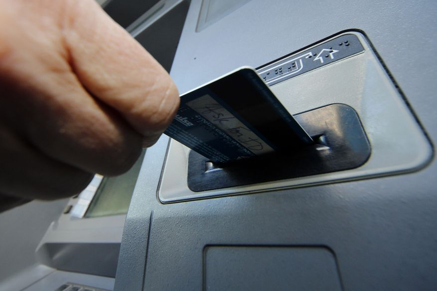 **FILE** A person demonstrates using a credit card in an ATM machine in Pittsburgh on Jan. 5, 2013. (Associated Press)