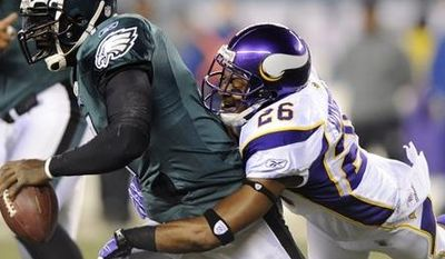 Philadelphia Eagles' Michael Vick, left, is tackled by Minnesota Vikings' Antoine Winfield in the first half of an NFL football game, Tuesday, Dec. 28, 2010, in Philadelphia. (AP Photo/Michael Perez)