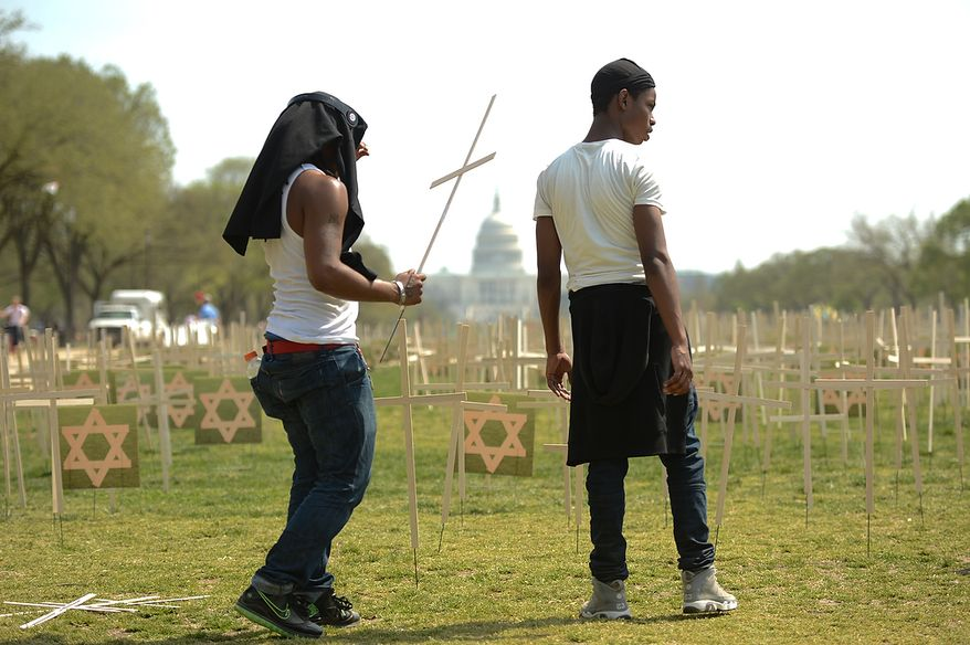 Bravon Freeman, 18, right, and another volunteer with Park View Kids Zone in Northwest, left, helps put down thousands of grave markers to represent victims of gun violence on the National Mall, Washington, D.C., Thursday, April 11, 2013. Religious leaders around the country begin a 24-hour vigil to honor the victims of gun violence since the shooting in Newtown.(Andrew Harnik/The Washington Times)