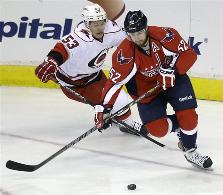 Carolina Hurricanes center Jeff Skinner (53) chases after Washington Capitals defenseman Mike Green (52) during the first period of an NHL hockey game on Thursday, April 11, 2013, in Washington. (AP Photo/Evan Vucci)