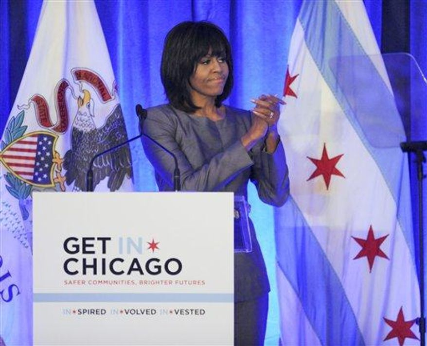 First lady Michelle Obama says goodbye to the crowd after speaking during a luncheon at the Chicago Hilton in Chicago, Wednesday, April 10, 2013. The first lady is visiting Chicago for a discussion with Chicago Mayor Rahm Emanuel and civic leaders on ways to combat youth violence. (AP Photo/Paul Beaty)