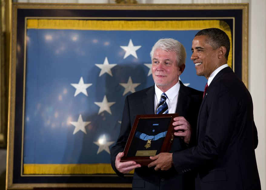 President Barack Obama stands with Ray Kapaun, nephew of Chaplain (Captain) Emil J. Kapaun, U.S. Army, as he awards the Medal of Honor posthumously to Chaplain Kapaun in the East Room of the White House in Washington on April 11, 2013. (Associated Press)