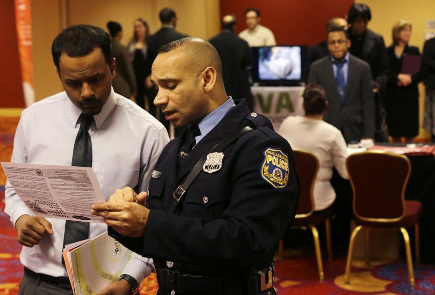 Officer Samuel Cruz (right), a Philadelphia police recruiter, talks with Ismail Azeer of Carteret, N.J., at the Edison Career Fair in the Iselin section of Woodbridge Township, N.J., on Tuesday, Feb. 26, 2013. (AP Photo/Mel Evans)
