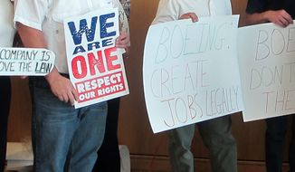 **FILE** Protesters hold signs outside a U.S. House Committee on Oversight and Government Reform field hearing on a National Labor Relations Board complaint against Boeing Co., in North Charleston, S.C., on June 17, 2011. (Associated Press)