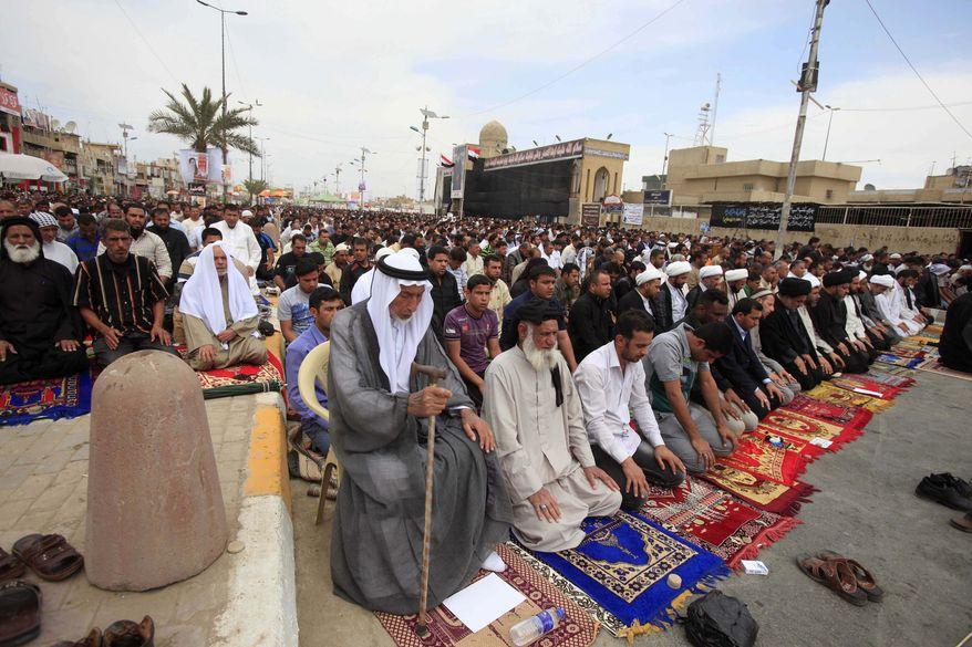 ** FILE ** Followers of radical Shiite cleric Muqtada al-Sadr attend Friday prayers in the Sadr City neighborhood in Baghdad, Iraq, Friday, March. 29, 2013. (AP Photo/Karim Kadim)