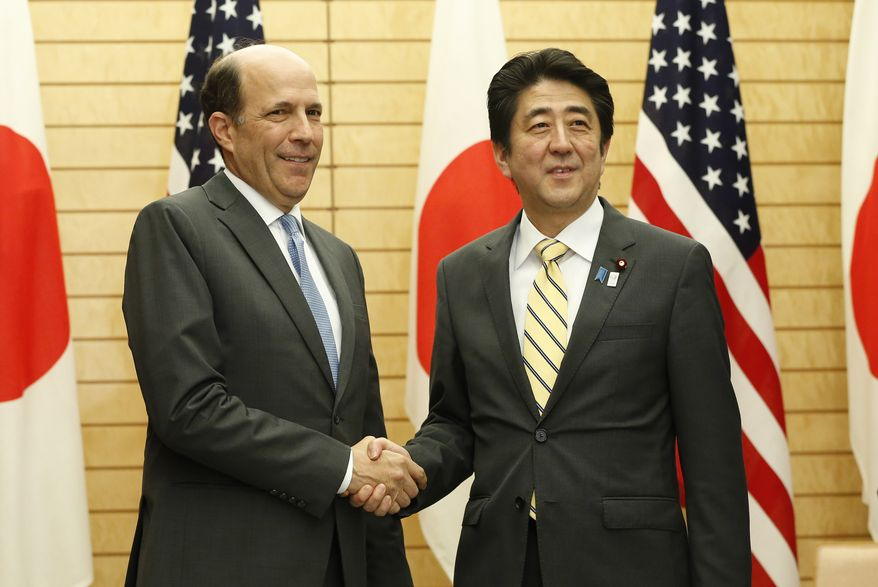**FILE** Japanese Prime Minister Shinzo Abe (right) shakes hands with U.S. Ambassador to Japan John Roos during a joint announcement at Abe's official residence in Tokyo on April 5, 2013. Japan and the U.S. have agreed on plans for returning to Japan land adjacent to Kadena Air Base on the southern island of Okinawa that is now used by the U.S. military. (Associated Press)