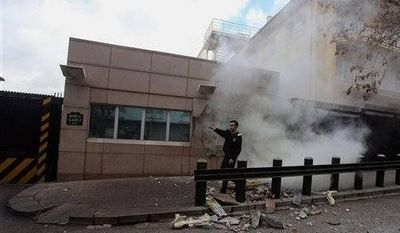 ** FILE ** An embassy security guard asks for help at the U.S. Embassy just minutes after a suicide bomber has detonated an explosive device at the entrance of the U.S. Embassy in the Turkish capital, Ankara, Turkey, Friday, Feb. 1. (Associated Press)
