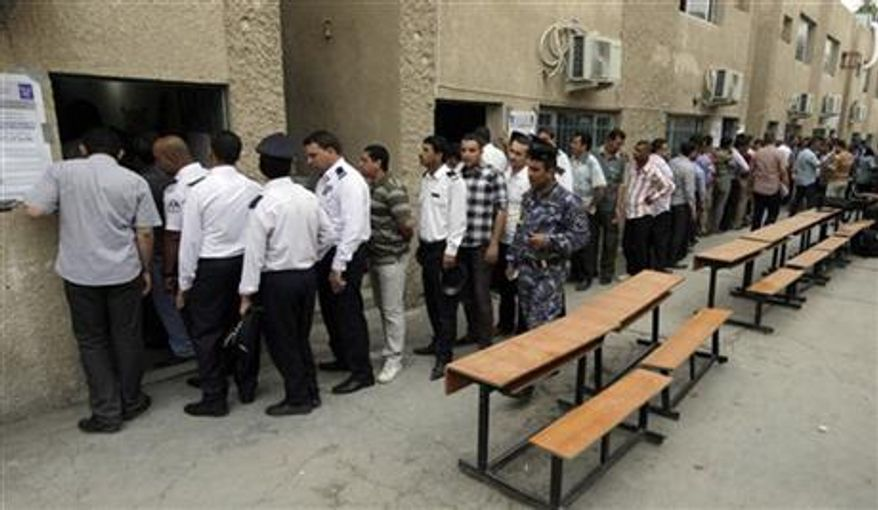 Iraqi security forces queue to vote at a polling center during the early voting in Baghdad, Iraq, Saturday, April 13, 2013. Voters head to the polls next week for the first time since the U.S. military withdrawal. (AP Photo/ Khalid Mohammed)