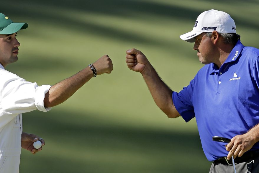 Angel Cabrera, of Argentina, fist bumps his caddie son Angel Cabrera, Jr. after a birdie on the 10th hole during the third round of the Masters golf tournament Saturday, April 13, 2013, in Augusta, Ga. (AP Photo/Charlie Riedel)