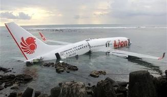 The wreckage of a crashed Lion Air plane sits on the water near the airport in Bali, Indonesia on Saturday, April 13, 2013. The plane carrying more than 100 passengers and crew overshot a runway on the Indonesian resort island of Bali on Saturday and crashed into the sea, injuring nearly two dozen people, officials said. (AP Photo/Indonesian Police)