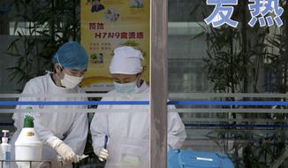 Nurses collect patients' blood samples at a specialized fever clinic inside the Ditan Hospital, where a Chinese girl is being treated for the H7N9 strain of bird flu, in Beijing on Sunday, April 14, 2013. (AP Photo/Andy Wong)