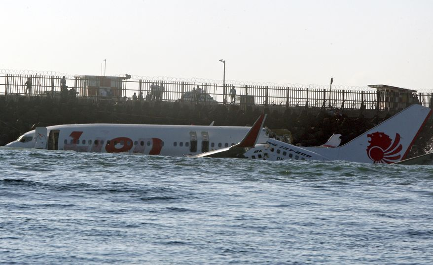 The wreckage of a Lion Air Boeing 737-800 sits in the ocean near the airport in Bali, Indonesia, on Sunday, April 14, 2013. All 108 passengers and crew survived after the new aircraft crashed into the ocean and snapped into two while attempting to land Saturday on the Indonesian resort island. (AP Photo/Firdia Lisnawati)