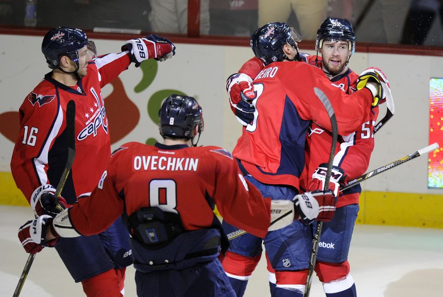 Washington Capitals defenseman Mike Green, right, celebrates his game-winning goal in the overtime period of an NHL hockey game with Eric Fehr (16), Alex Ovechkin (8), of Russia, and Mike Ribeiro, second from right, against the Tampa Bay Lightning, Saturday, April 13, 2013, in Washington. The Capitals won 6-5 in overtime. (AP Photo/Nick Wass)