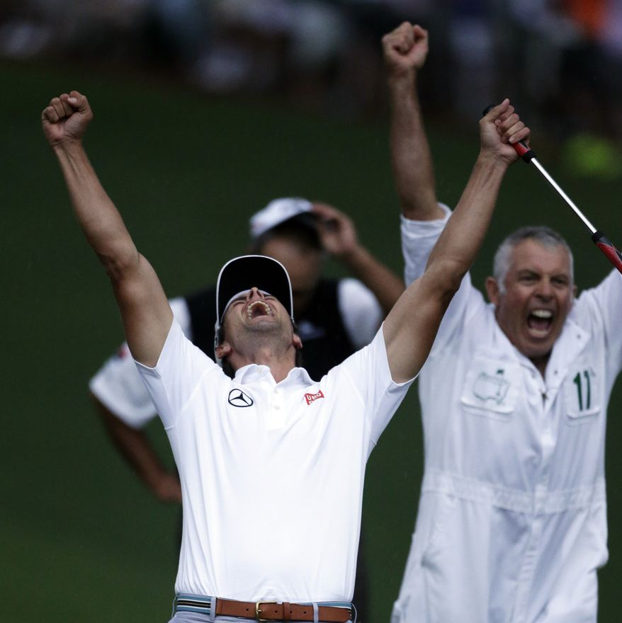 Adam Scott, of Australia, celebrates with caddie Steve Williams after making a birdie putt on the second playoff hole to win the Masters golf tournament Sunday, April 14, 2013, in Augusta, Ga. (AP Photo/Darron Cummings)