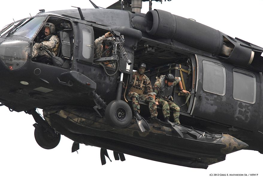 """SEALs sit ready in the doorways with their Zodiac suspended below at US Army  HH-60H Seahawk belonging to the 160th Special Operations Aviation Regiment (SOAR) """"NIght on Stalkers"""", as they prepare for a water insertion.  Photo: Greg E. Mathieson Sr. / NSW Publications, LLC"""