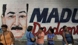 Venezuelans wait to enter a polling station where a nearby wall is covered with a mural of Interim President Nicolas Maduro during the presidential election in Caracas, Venezuela, on Sunday, April 14, 2013. (AP Photo/Ariana Cubillos)