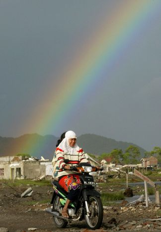 **FILE** Acehnese women ride a motorcycle as rainbow fills the sky after a rain in the village of Lampaseh Aceh in the provincial capital of Banda Aceh, Indonesia, on June 18, 2005. (Associated Press)