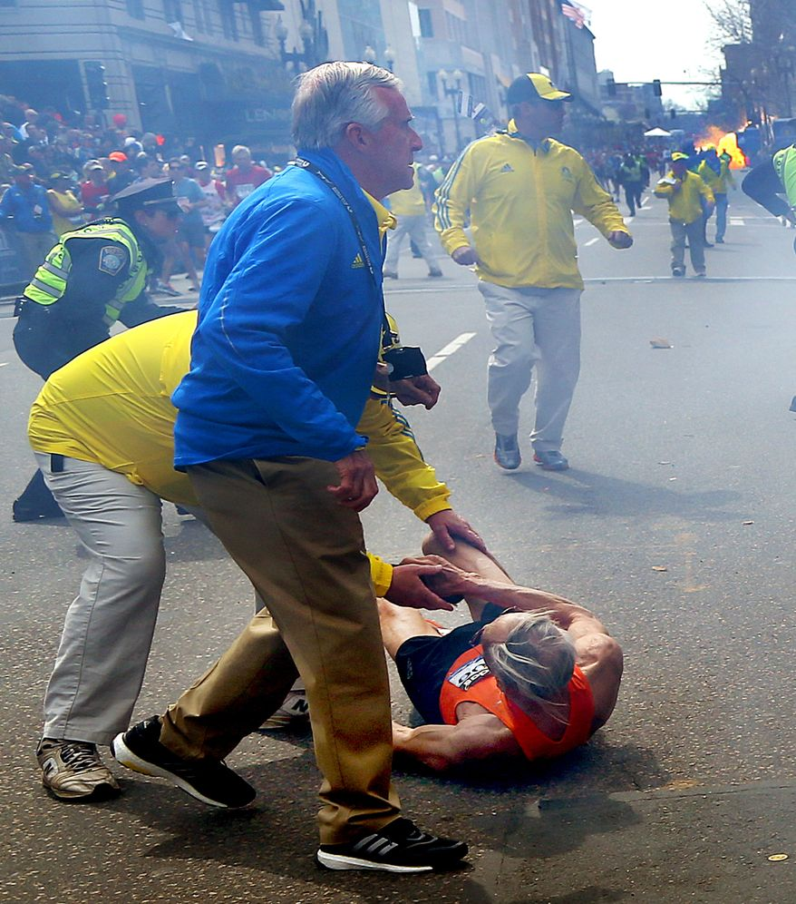 People react to a second explosion at the 2013 Boston Marathon in Boston, Monday, April 15, 2013. Two explosions shattered the euphoria of the Boston Marathon finish line on Monday, sending authorities out on the course to carry off the injured while the stragglers were rerouted away from the smoking site of the blasts. (AP Photo/The Boston Globe, John Tlumacki)