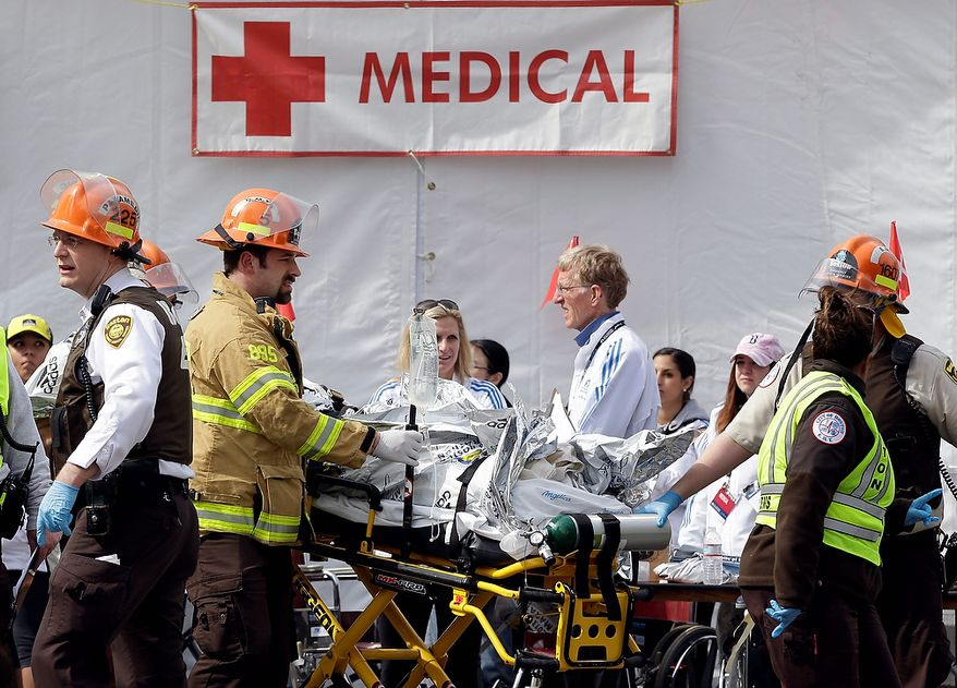 Medical personnel work outside the medical tent in the aftermath of two blasts which exploded near the finish line of the Boston Marathon in Boston, Monday, April 15, 2013. (AP Photo/Elise Amendola)