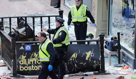 Boston police clear an area following an explosion near the finish line of the 2013 Boston Marathon in Boston, Monday, April 15, 2013. Two explosions shattered the euphoria of the Boston Marathon finish line on Monday, sending authorities out on the course to carry off the injured while the stragglers were rerouted away from the smoking site of the blasts. (AP Photo/Charles Krupa)