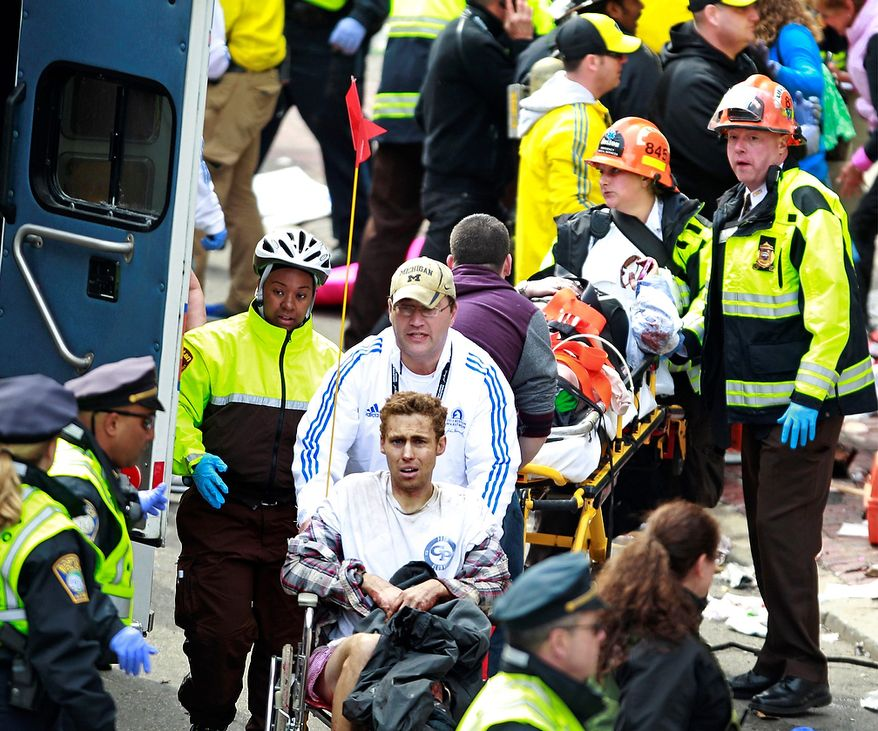 Medical workers aid injured people at the finish line of the 2013 Boston Marathon following an explosion in Boston, Monday, April 15, 2013. Two explosions near the finish of the Boston Marathon on Monday, killing at least  two people, injuring over 20 others. (AP Photo/Charles Krupa)