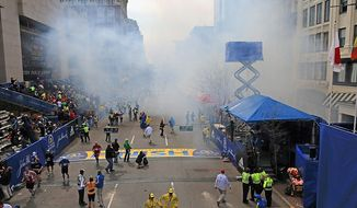 Medical workers aid injured people at the 2013 Boston Marathon following an explosion in Boston, Monday, April 15, 2013. Two explosions shattered the euphoria of the Boston Marathon finish line on Monday, sending authorities out on the course to carry off the injured while the stragglers were rerouted away from the smoking site of the blasts. (AP Photo/The Boston Globe, David L Ryan)