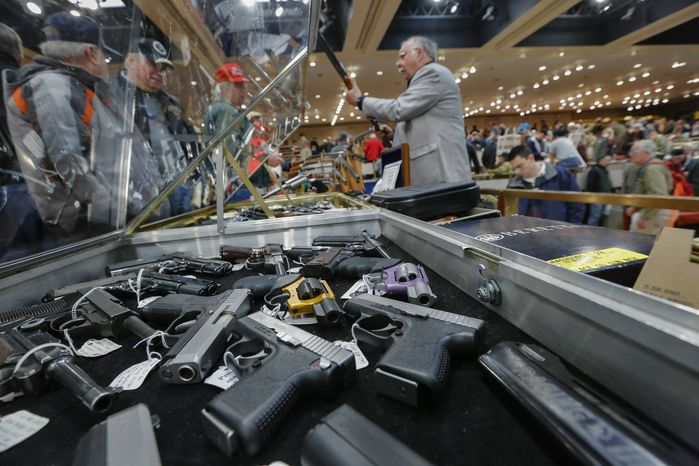 * *FILE ** Handguns are displayed at the table of David Petronis (standing with rifle) of Mechanicville, N.Y.,  who owns a gun store, during the heavily attended annual New York State Arms Collectors Association Albany Gun Show at the Empire State Plaza Convention Center in Albany, N.Y., on Jan. 26, 2013. (Associated Press)