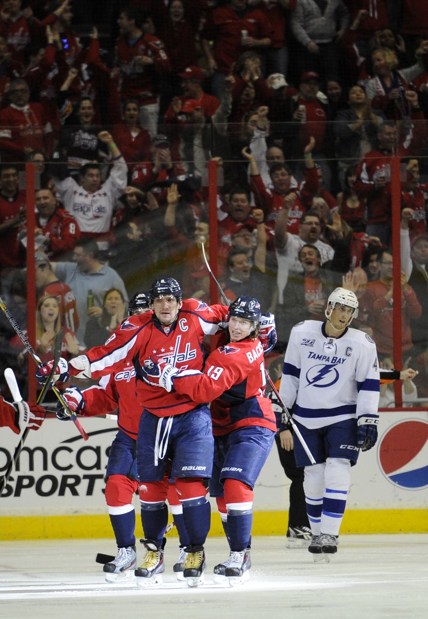 Washington Capitals left wing Alex Ovechkin (8), of Russia, celebrates his goal with teammate Nicklas Backstrom (19), of Sweden, as Tampa Bay Lightning center Vincent Lecavalier (4) looks on at back right, during the second period of an NHL hockey game, Sunday, April 7, 2013, in Washington. (AP Photo/Nick Wass)