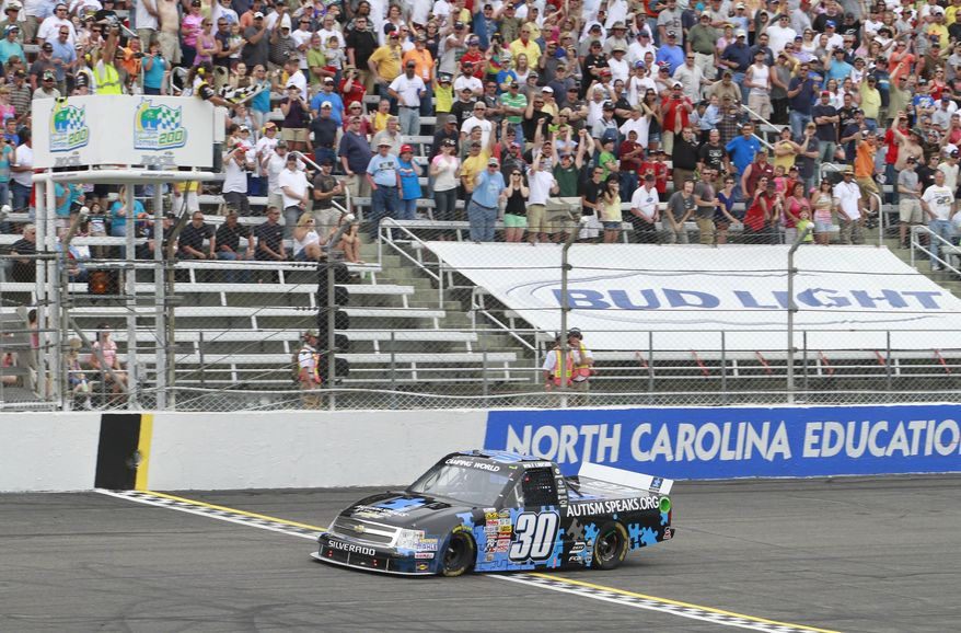 Kyle Larson (30) takes the checker flag to win the North Carolina Education Lottery 200 race in the NASCAR Camping World Truck Series in Rockingham, N.C., Sunday, April 14, 2013. (AP Photo/Jim R. Bounds)