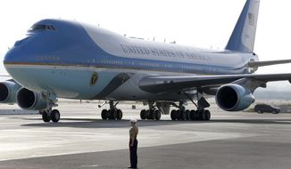 ** FILE ** A Marine officer stands watch as Air Force One, with President Obama on board, arrives at San Francisco International Airport outside San Francisco on Wednesday, April 3, 2013. (AP Photo/Tony Avelar)