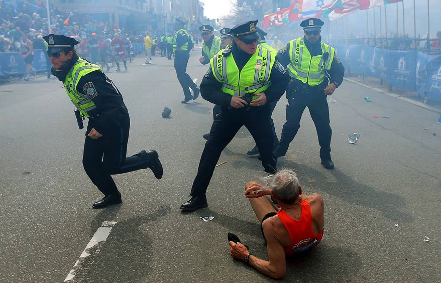 ** FILE ** Bill Iffrig, 78, lies on the ground as police officers react to a second explosion at the finish line of the Boston Marathon in Boston, Monday, April 15, 2013. Iffrig, of Lake Stevens, Wash., was running his third Boston Marathon and near the finish line when he was knocked down by one of two bomb blasts. (AP Photo/The Boston Globe, John Tlumacki)