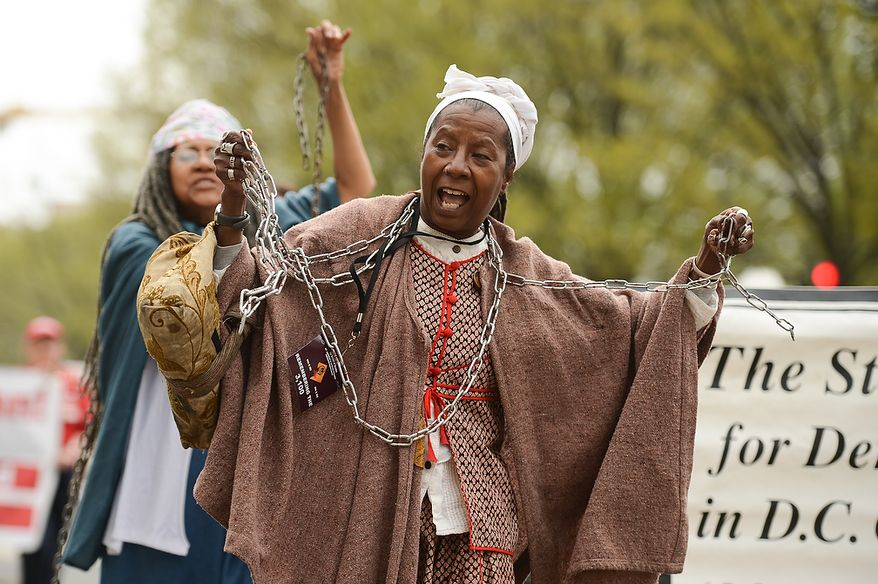 Ayo Handy-Kendi, center, and others wears chains to show their opposition to the district not having a voting representative in congress as she participates in the Washington, D.C. Emancipation Day parade, Washington, D.C., Tuesday, April 16, 2013. President Abraham Lincoln freed approximately 3,100 slaves in the District of Colombia on April 16, 1862, nine months before the Emancipation Proclamation. (Andrew Harnik/The Washington Times)