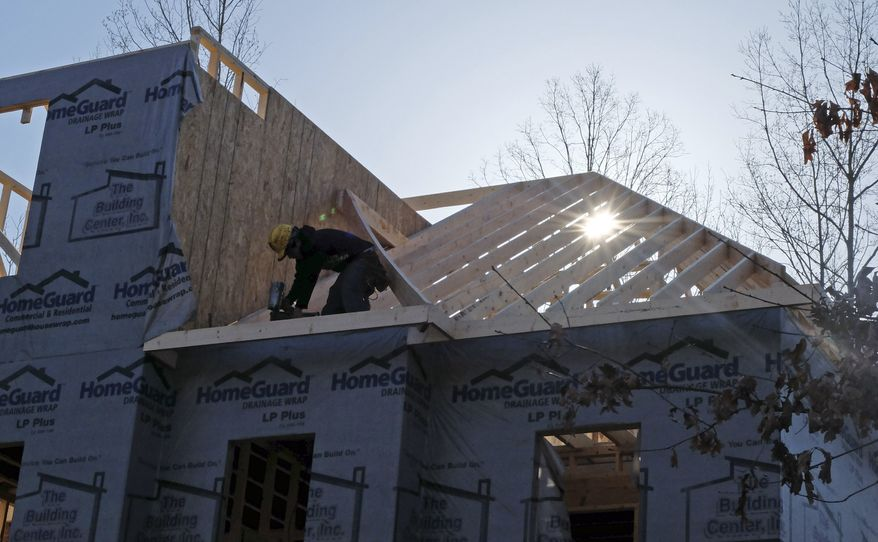 A worker helps frame a new home under construction in Matthews, N.C., on Friday, March 29, 2013. (AP Photo/Chuck Burton)