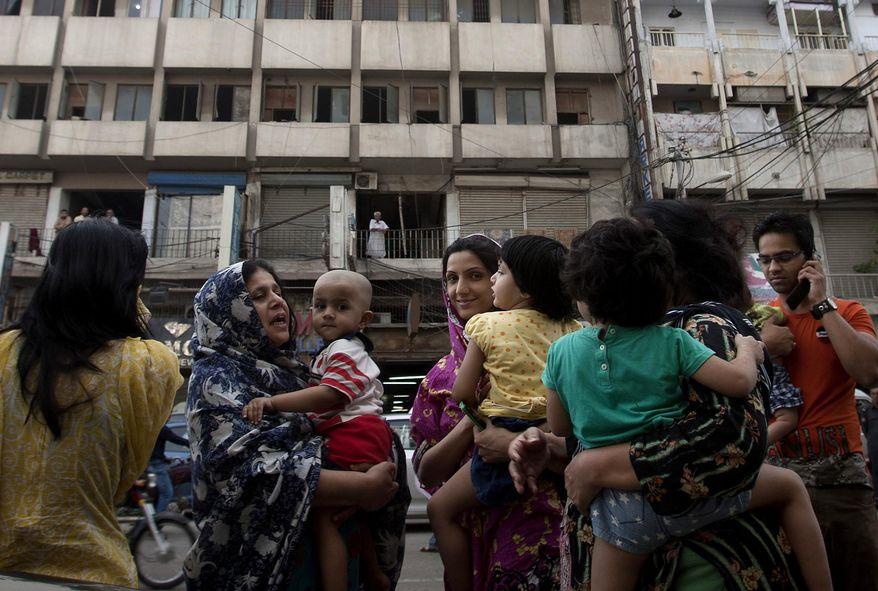 People evacuate buildings as an earthquake was felt in Karachi, Pakistan, Tuesday, April 16, 2013. (AP Photo/Shakil Adil)