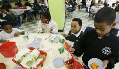 ** FILE ** A student serves up dessert to classmates during lunch at the People for People Charter School on Monday, Feb. 25, 2013, in Philadelphia. (AP Photo/Matt Rourke)