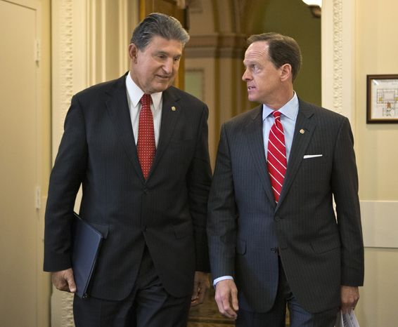 ** FILE ** Sens. Joe Manchin III (left), West Virginia Democrat, and Patrick J. Toomey, Pennsylvania Republican, arrive on Wednesday, April 10, 2013, for a news conference on Capitol Hill in Washington to announce that they have reached a bipartisan deal on expanding background checks to more gun buyers. (Associated Press)