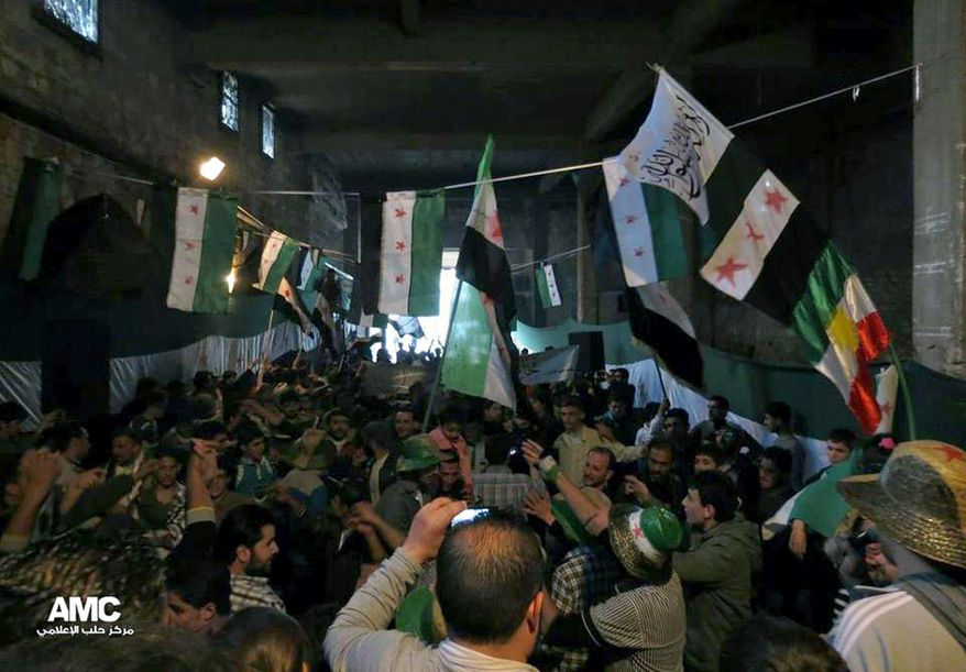 Anti-Syrian-regime protesters holding Syrian revolution flags during a rally marking the anniversary of the 1946 withdrawal of French troops from Syria, which marked the end of France's mandate of the Arab country, in the old quarter of the northern city of Aleppo, Syria, on Wednesday, April 17, 2013. (AP Photo/Aleppo Media Center AMC)