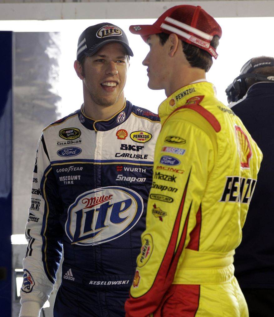 Drivers Brad Keselowski, left, and Joey Logano talk in the garage during practice for Sunday's NASCAR Sprint Cup series auto race at Martinsville Speedway in Martinsville, Va., Friday, April 5, 2013. (AP Photo/Steve Helber)