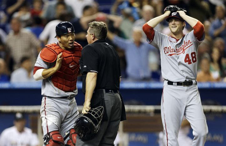 Washington Nationals catcher Kurt Suzuki and left-hander Ross Detwiler react to what appeared to be a blown call by home plate umpire Greg Gibson in the fifth inning Wednesday night against the Miami Marlins. (Associated Press photo)