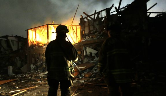 Firefighters use flashlights to search a destroyed apartment complex near a fertilizer plant that exploded earlier in West, Texas, in this photo taken early on Thursday, April 18, 2013. (AP Photo/LM Otero)