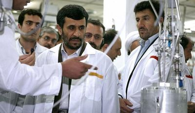 ** FILE ** Iranian President Mahmoud Ahmadinejad (center) listens to a technician during his visit to the Natanz Uranium Enrichment Facility some 200 miles south of the capital, Tehran, in April 2008. (AP Photo/Iranian President's Office)