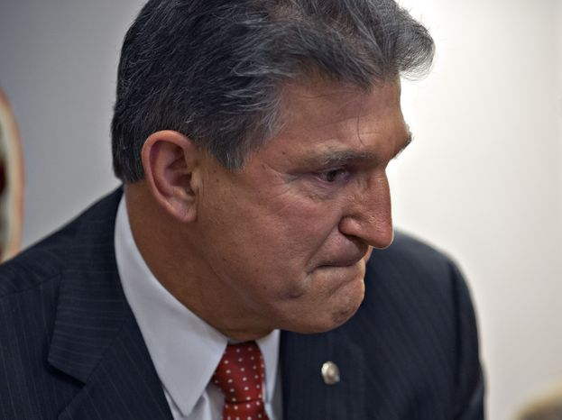 ** FILE ** Sen. Joe Manchin, D-W.Va., becomes emotional as he meets in his office with families of victims of the Sandy Hook Elementary School shooting in Newtown, Conn., on the day he announced that they have reached reached a bipartisan deal on expanding background checks to more gun buyers, at the Capitol in Washington, Wednesday, April 10, 2013. (AP Photo/J. Scott Applewhite)