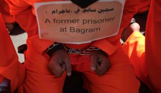 A former Yemeni prisoner at the Bagram prison in Afghanistan, dressed in an orange prison uniform, protests in front of the U.S. Embassy in Sanaa, Yemen, on Tuesday, April 16, 2013, to  demand the release of Yemeni detainees in the Guantanamo Bay prison. (AP Photo/Hani Mohammed)