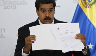 ** FILE ** Venezuelan Interim President Nicolas Maduro holds the official certificate declaring him the winner of the presidential election, at the Electoral Council in Caracas, Venezuela, on Monday, April 15, 2013. The nation's government-friendly Electoral Council quickly certified the razor-thin presidential victory of the late President Hugo Chavez's hand-picked successor over challenger Henrique Capriles. (Associated Press)