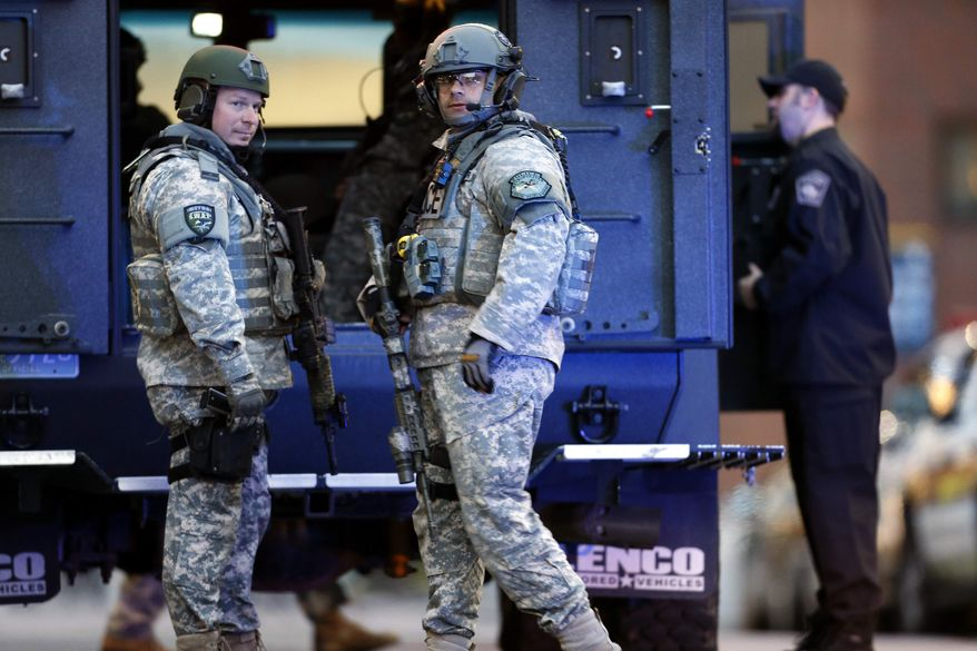 S.W.A.T. team members stand guard on the campus of Massachusetts General Hospital  following an explosion at the finish line of the Boston Marathon in Boston, Monday, April 15, 2013. (AP Photo/Michael Dwyer)