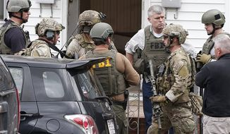 Heavily armed FBI agents gather next door to 410 Norfolk Street in Cambridge, Mass., Friday, April 19, 2013. Two suspects in the Boston Marathon bombing killed an MIT police officer, injured a transit officer in a firefight and threw explosive devices at police during a getaway attempt in a long night of violence that left one of them dead and another still at large Friday, authorities said as the manhunt intensified for a young man described as a dangerous terrorist. (AP Photo/Michael Dwyer)